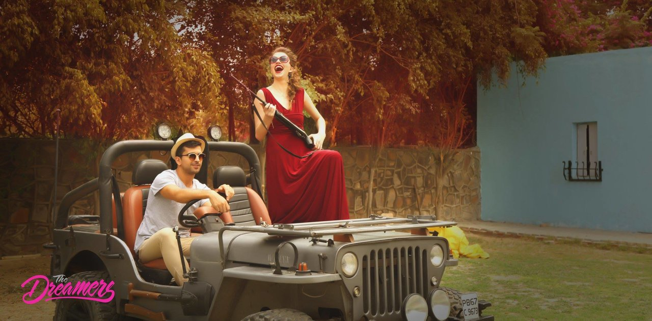 Safari style couple photoshoot | pre wedding shoot on a jeep with girl holding gun in red dress | Studio Future Forward | 5 Spectacular Photo Shoot Locations in Delhi NCR | FunctionMania