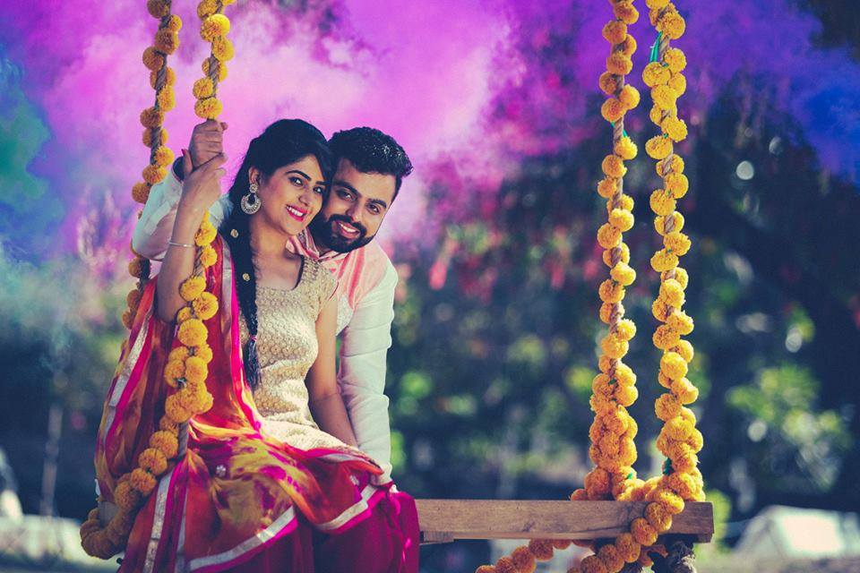 Romantic Pre Wedding photoshoot of a couple in swing with genda phool or marigold and background with multicolored hues and holi feel | Studio Future Forward | 5 Spectacular Photo Shoot Locations in Delhi NCR | FunctionMania