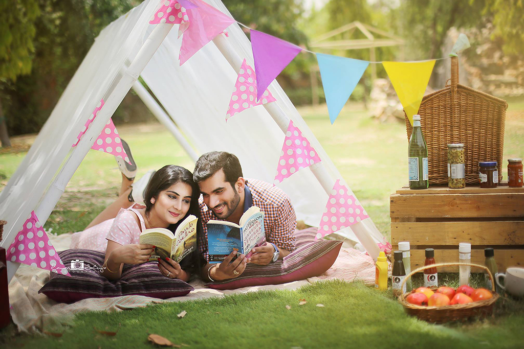 Camping couple reading books in garden under white tent with fruit baskets and champagne around | Picnic | colorful | | Studio Future Forward | 5 Spectacular Photo Shoot Locations in Delhi NCR | FunctionMania