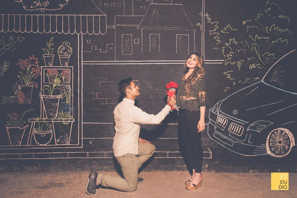 Romantic couple in front of a graffiti wall with car and plants sketch, the boy proposing the girl with red roses| Photo Paradise | 5 Spectacular Photo Shoot Locations in Delhi NCR | FunctionMania