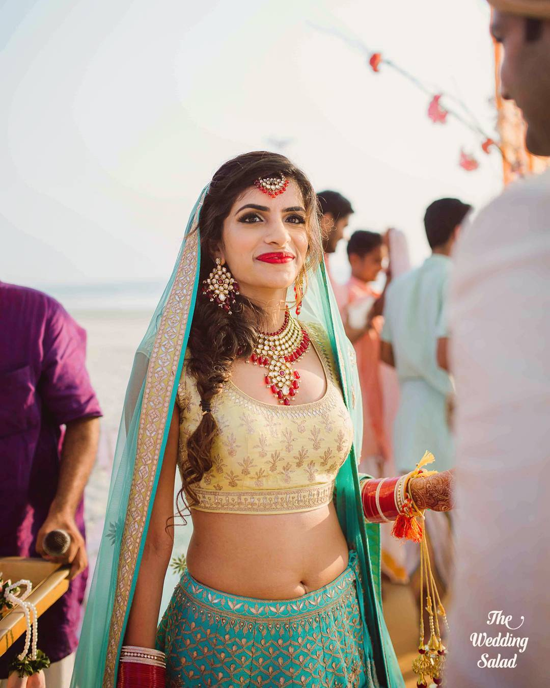 Turquoise lehenga with gota leaf work and golder top and contrasting red jewelry | 11 Unique Lehenga Hues That Will Make You Ditch The Usual Red | FunctionMania