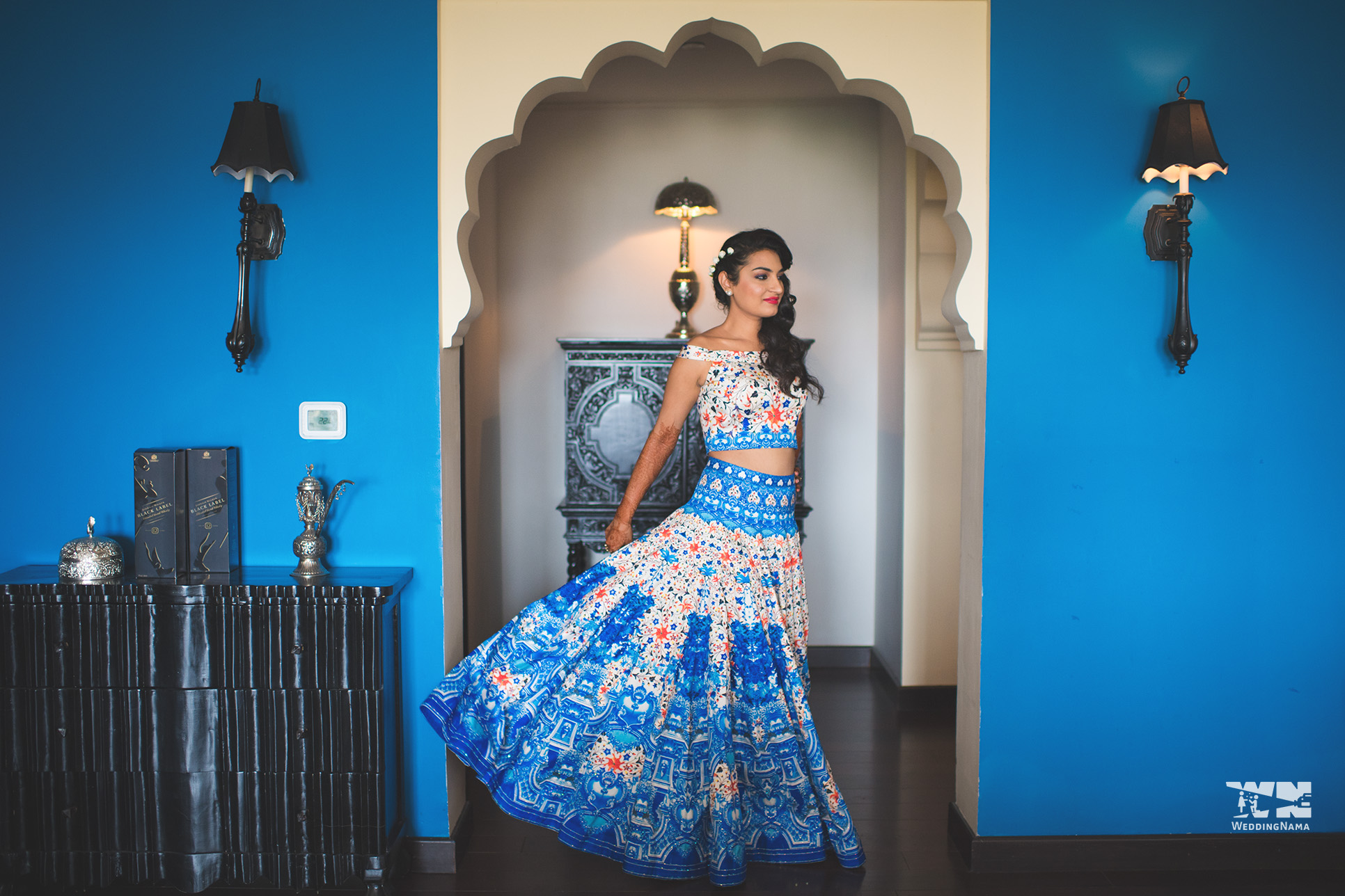 Classic Blue Backdrop Bride Posing in Royal Blue Digital Printed off shoulder Crop top with High Waist Skirt | 11 Unique Lehenga Hues That Will Make You Ditch The Usual Red | FunctionMania