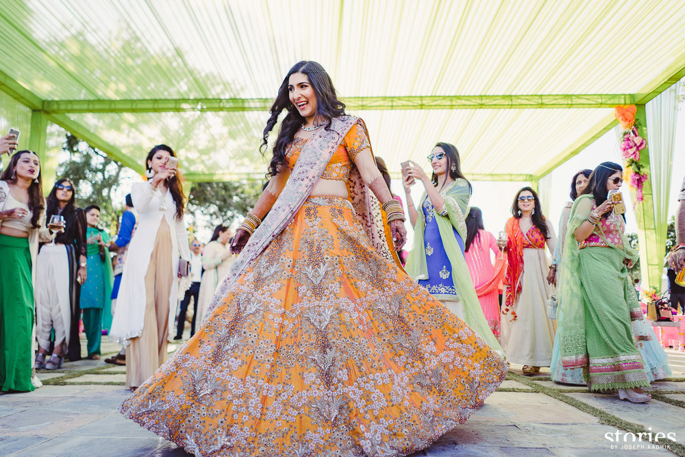 Twirling Bride in Orange Lehenga with scattered floral gota work and lavender pink dupatta | 11 Unique Lehenga Hues That Will Make You Ditch The Usual Red | FunctionMania