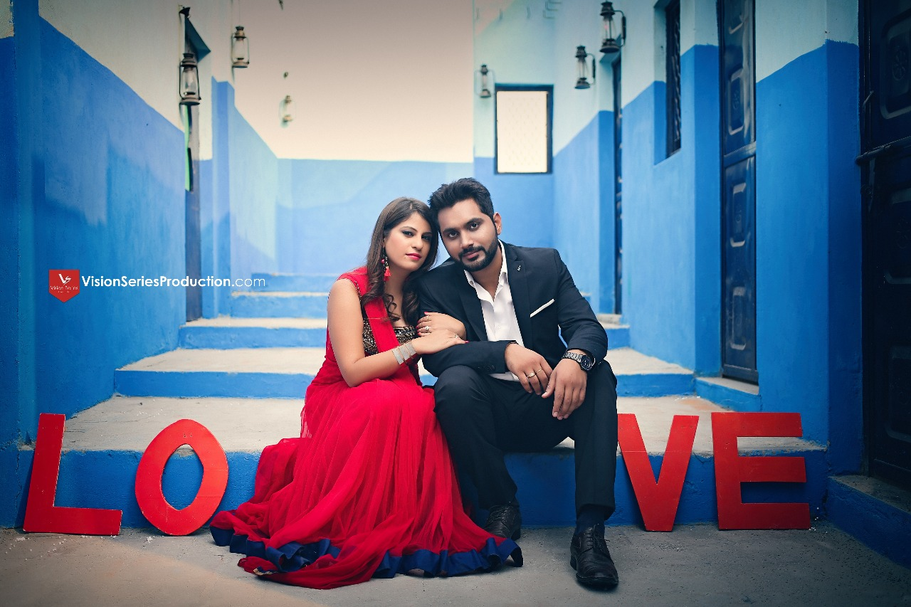 Very romantic photoshoot of a couple with royal blue street style backdrop with LOVE letters written | Your Dream Location | 5 Spectacular Photo Shoot Locations in Delhi NCR | FunctionMania
