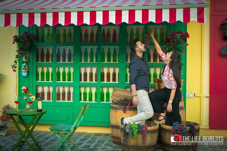 Romantic Pre Wedding Photoshoot of a couple with bar setting and red wine eating grapes at Picture Destination | 5 Spectacular Photo Shoot Locations in Delhi NCR | FunctionMania