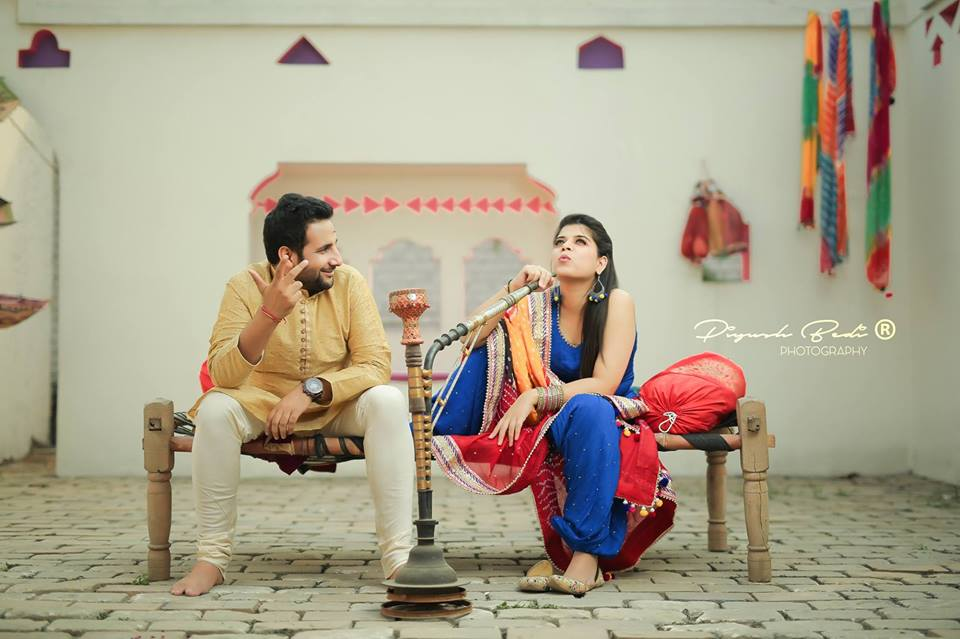 Indian couple having hukka on a charpai with a village background photoshoot for prewedding Picture Destination | 5 Spectacular Photo Shoot Locations in Delhi NCR | FunctionMania