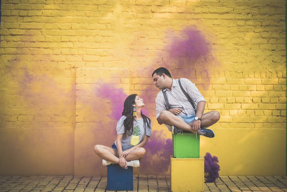 Couple's photoshoot sitting on colorful boxes and multicolored wall at Picture Destination | 5 Spectacular Photo Shoot Locations in Delhi NCR | FunctionMania