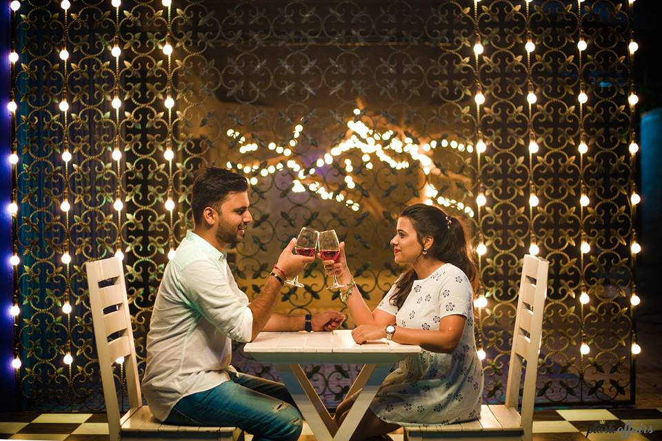 Candle light setting romantic photoshoot of couple having wine in fairy lights backdrop | 5 Spectacular Photo Shoot Locations in Delhi NCR | FunctionMania