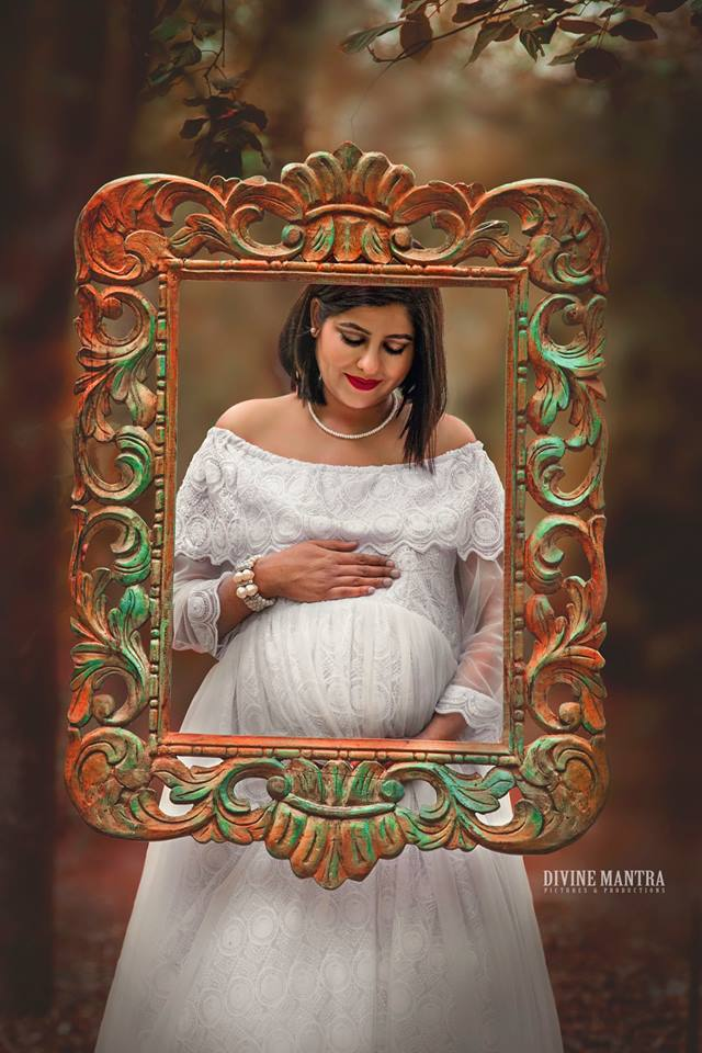 maternity photoshoot with a pretty backdrop and the mother in white dress | Photo Paradise | 5 Spectacular Photo Shoot Locations in Delhi NCR | FunctionMania