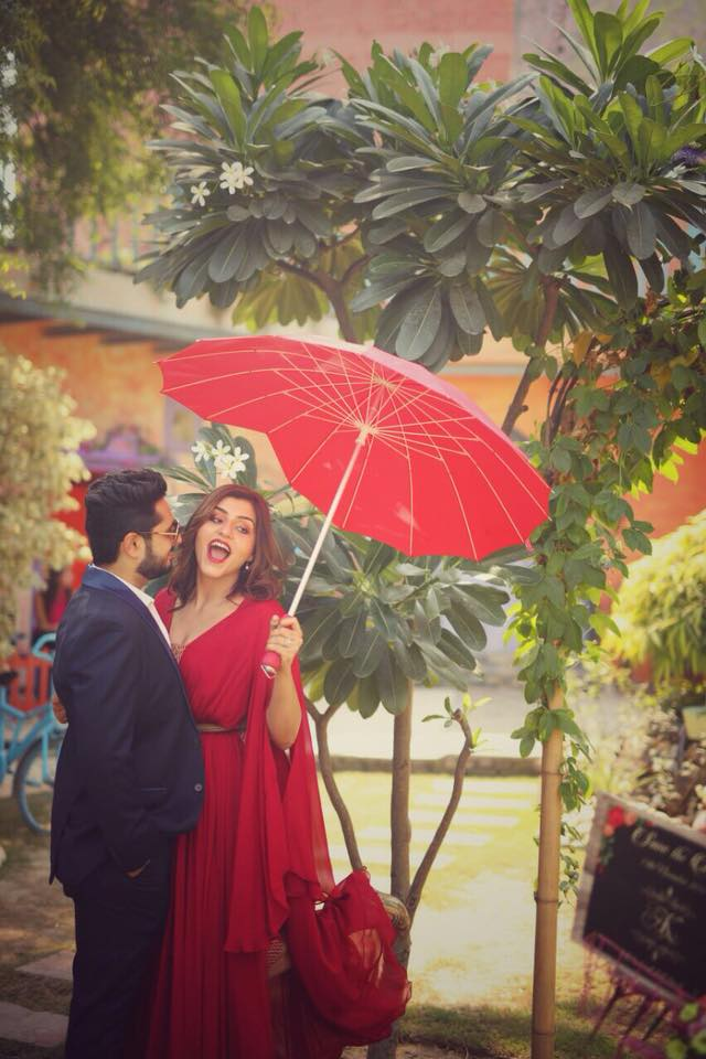 Very romantic and trendy pre wedding couple photoshoot in garden with white flowers, red umbrella prop and the girl in red dress | Photo Paradise | 5 Spectacular Photo Shoot Locations in Delhi NCR | FunctionMania