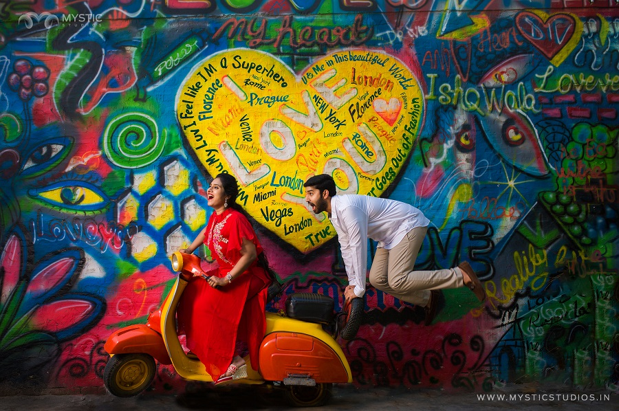 Cute romantic pre wedding photoshoot with the bride on a yellow and orange vintage scooter in a red dress and groom hanging behind in front of a graffiti wall with i love you painted | Photo Paradise | 5 Spectacular Photo Shoot Locations in Delhi NCR | FunctionMania