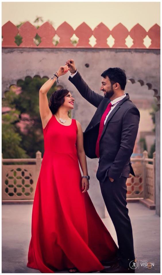 romantic couple photoshoot with girl in red dress and guy in tux wearing red tie at dusk | Photo Paradise | 5 Spectacular Photo Shoot Locations in Delhi NCR | FunctionMania