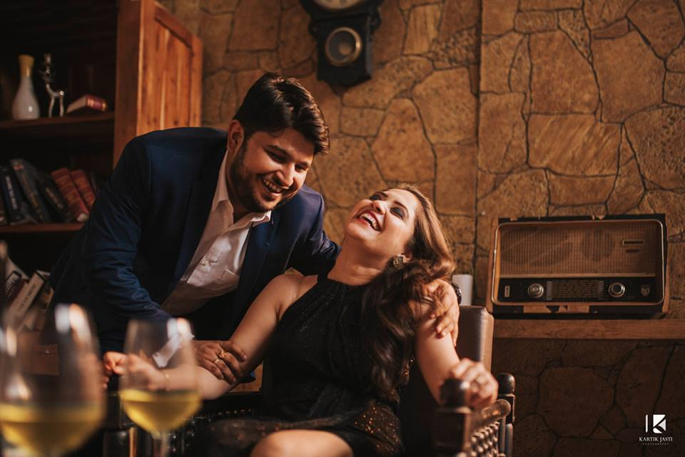 Couple photoshoot drinking wine and laughing with vintage room setting, a library and a vintage radio | Studio Future Forward | 5 Spectacular Photo Shoot Locations in Delhi NCR | FunctionMania