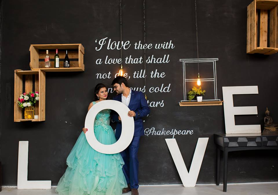 Romantic Couple Photoshoot with bride in a turquoise dress and groom in navy blue coat in front of an inscripted wall holding LOVE written. | Studio Future Forward | 5 Spectacular Photo Shoot Locations in Delhi NCR | FunctionMania
