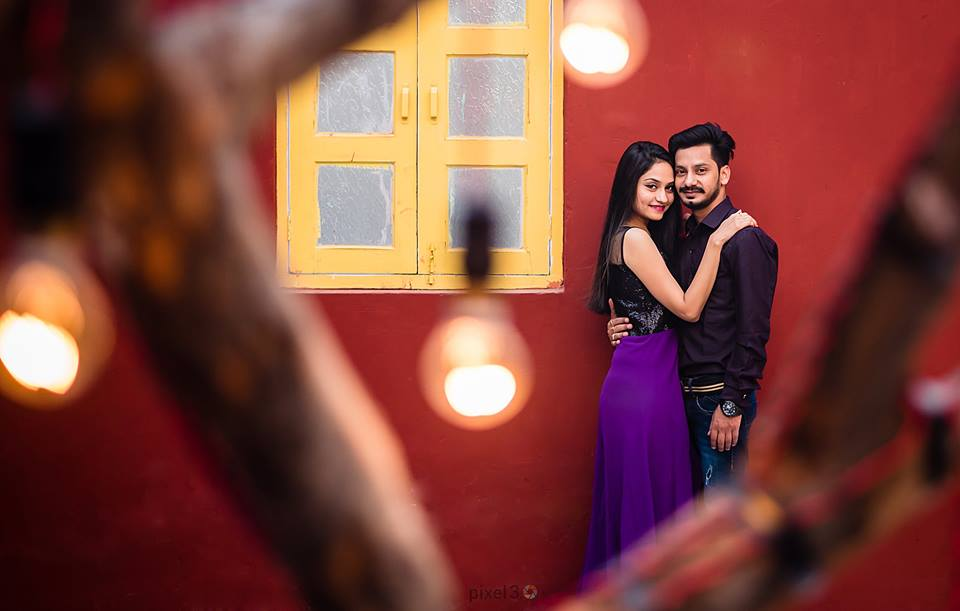 Amazing romantic photoshoot of a couple in lights and red wall with yellow window. Girl in black and violet dress and buy in burgundy shirt | Your Dream Location | 5 Spectacular Photo Shoot Locations in Delhi NCR | FunctionMania