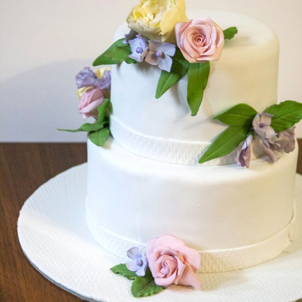 White pastel sugary flowers and green petals wedding cake by TheBakers.in