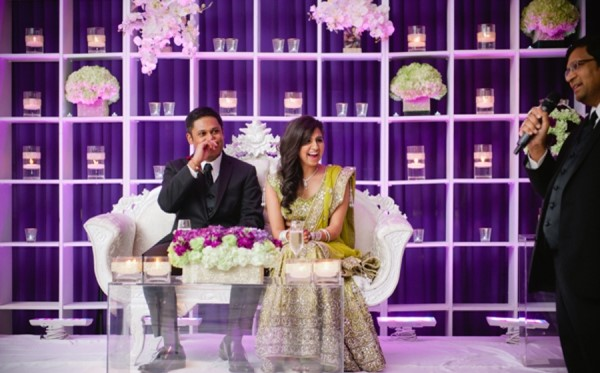 Indian Couple at an engagement party | stage decor | ultra violet | Candles for backdrop decor | Function Mania | #Trending: How to use hues of Ultraviolet for a chic wedding decor!