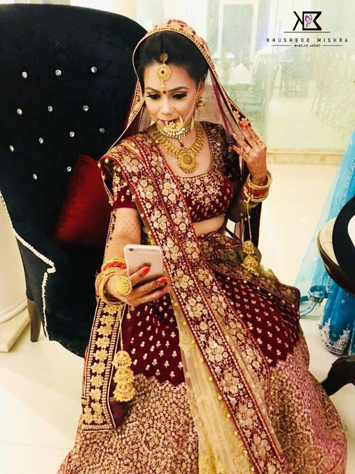 Indian Bride Clicking selfie in Maroon Lehenga with Golden Jewellery and Beautiful Makeup and Hairstyle-