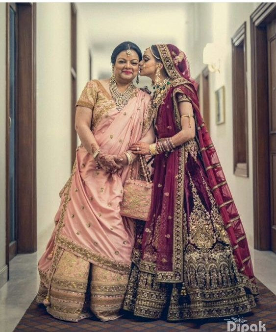 Bride kissing mom on cheek | Peach an Golden Lehenga for Mom-of-the-bride | Maroon and Golden Lehenga for Indian Bride | Mom and Bride Picture Ideas | Cute Bride and Mother Photo Ideas | Indian Wedding | Indian Brides | Function Mania | You Have to See These Picture-Perfect Mother & Bride Moments!