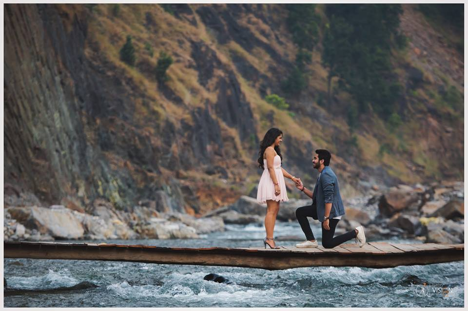 Girl in white dress with guy on his knees on a pier | Prewedding Photoshoot ideas | Beach side couple photography | Couple Goals | Third Vision Studio | Function Mania