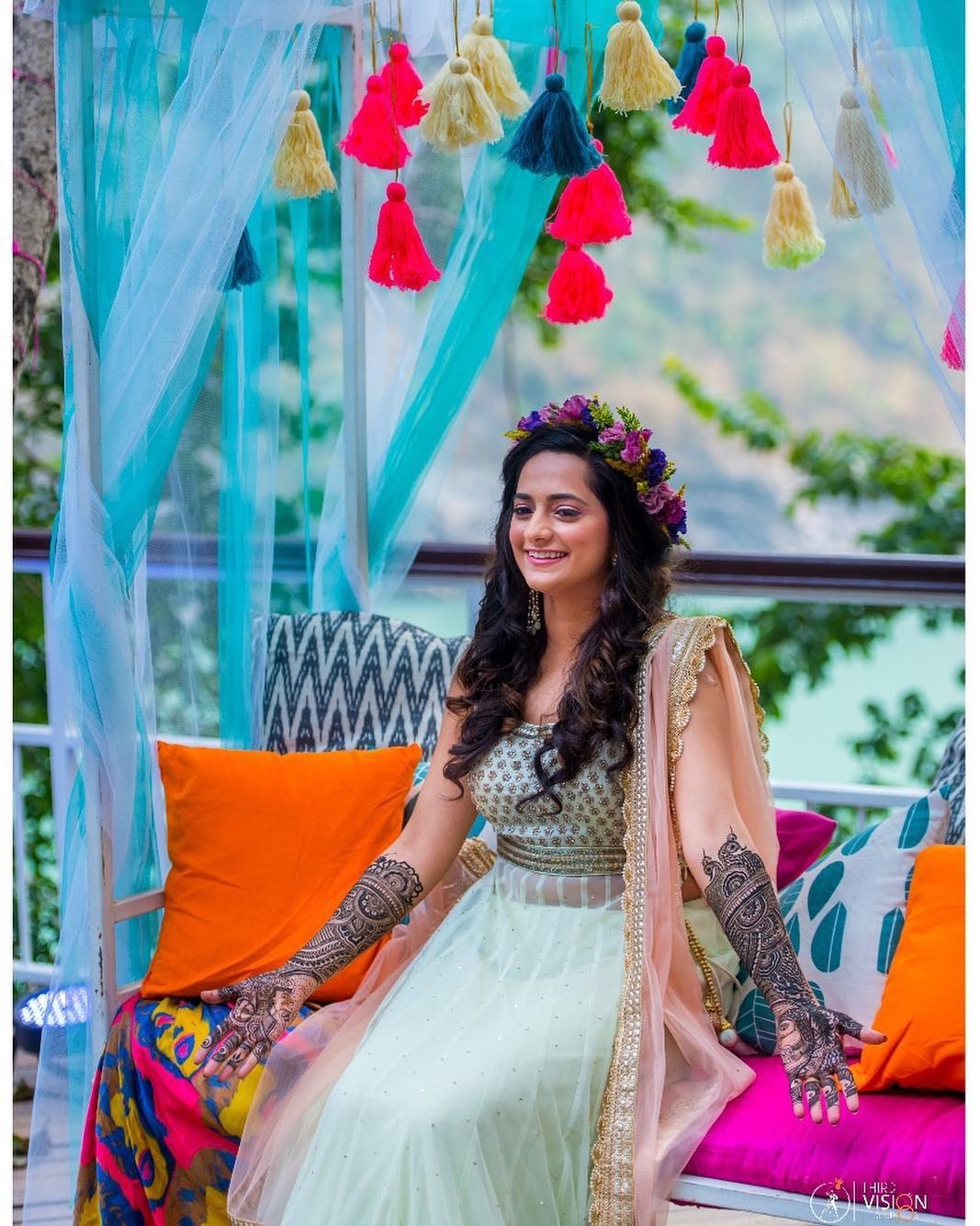 BRIDE SMILING ON HER MEHENDI FUNCTION | PASTEL MINT AND PEACH LEHENGA FOR MEHENDI | FLORAL TIARA FOR BRIDES | TASSELS FOR MEHENDI DECOR | LIGHT BLUE SHEER CURTAINS FOR WEDDING DECOR \ THRID VISION STUDIO | FUNCTION MANIA