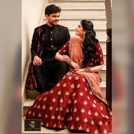 Bride in beautiful red lehenga with pretty embroidery | Groom in traditional sherwani with gorgeous sherwani dupatta | Bride And Groom posing for a picture on a staircase | Engagement Couple Photography | Couple Photoshoots | Lenseyezia Productions | Function Mania