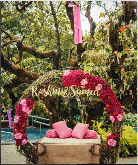 huge floral wreath for a beautiful couple seating at a Mehendi ceremony | Mehendi decor ideas | Wreath Decor Ideas with Couples Name | Function Mania