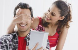 Woman giving present to man   Surefire tips to Throw a Surprise Birthday Party For Him If You Are Low On Budget!   Function Mania  