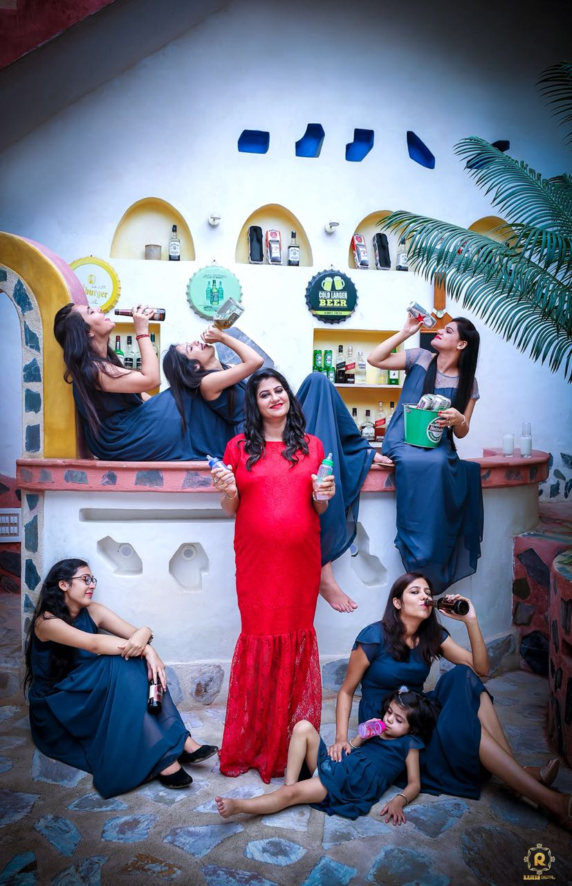 Quirky maternity photoshoot with Indian mom-to-be posing with a milk bottle and bridesmaids posing with beer bottles