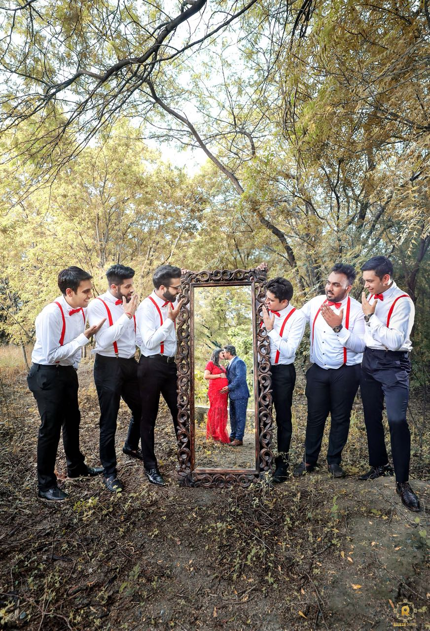 Parents-to-be sharing a romantic kiss and groomsmen holding the mirror for them
