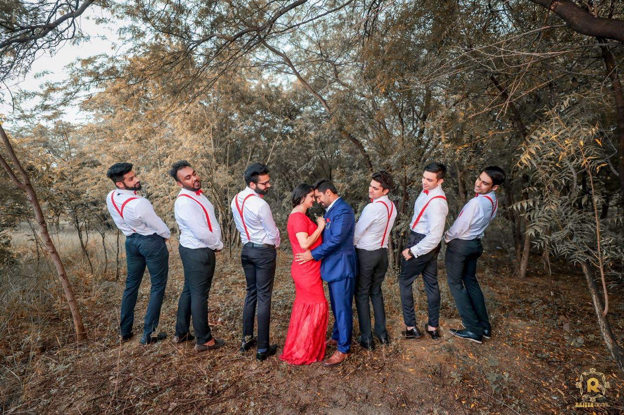 Cute pose for groomsmen with expecting couple dressed in a red dress and blue tuxedo