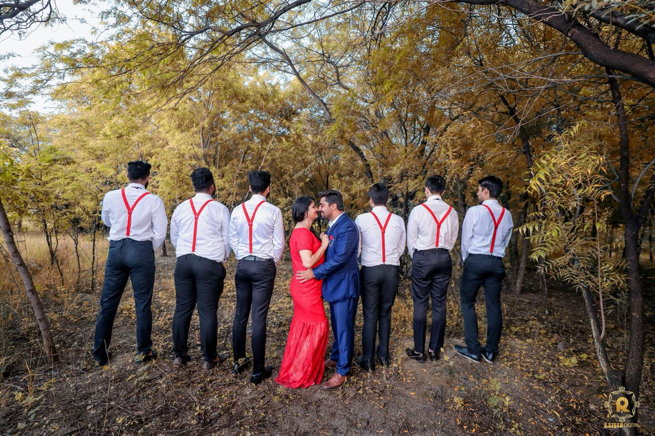 Unique pose for groomsmen with couple for a maternity shoot in a wild environment