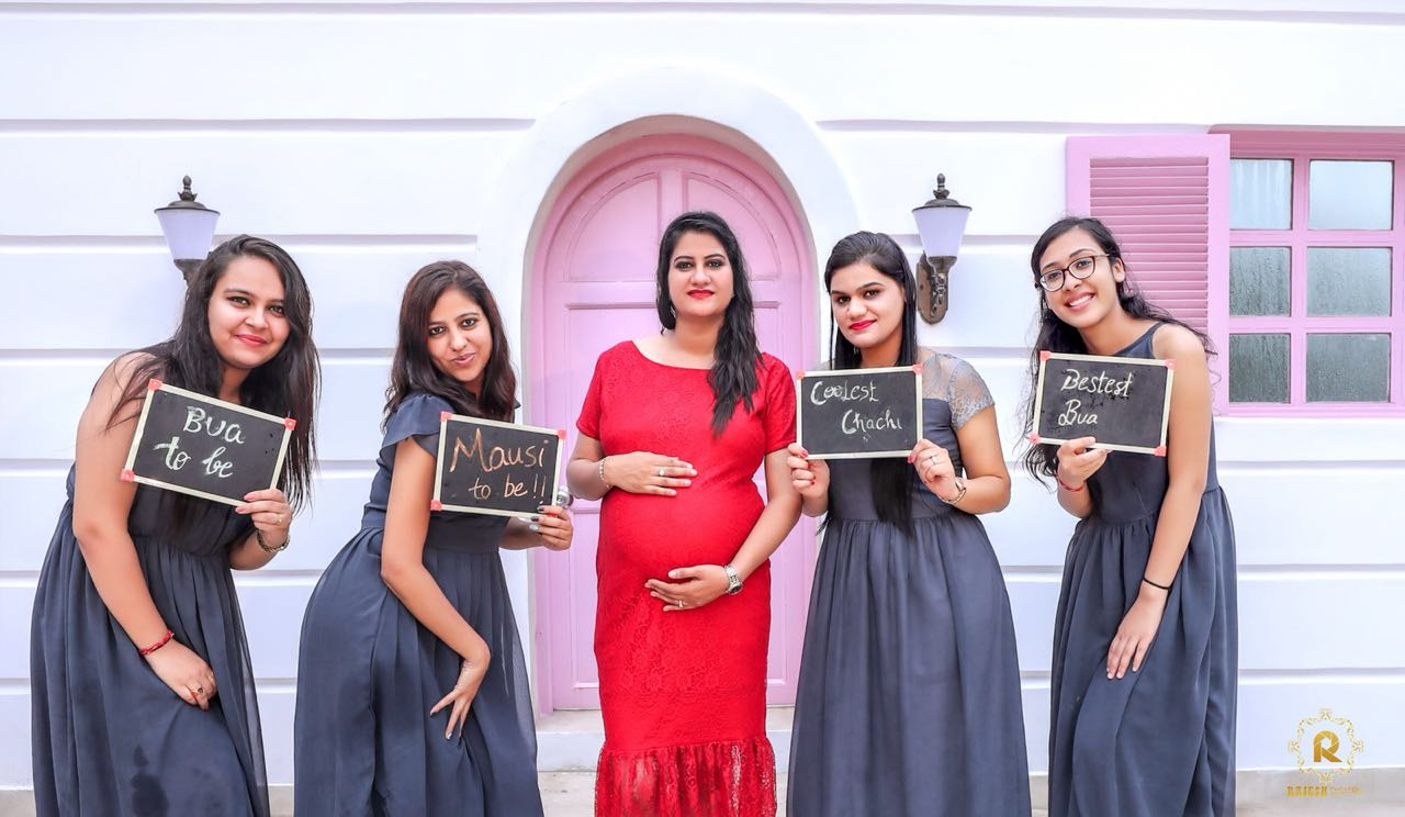 Bua-to-be, Mausi-to-be, Chachi-to-be, Bestest Bua tags with bridesmaids in a slate grey dress and mom-to-be in a red dress for a unique maternity shoot
